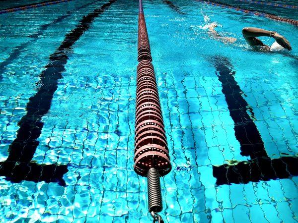 Foto de uma piscina com raia, com uma pessoa nadando.