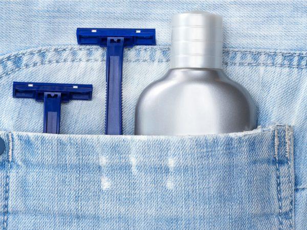 Imagem mostra um frasco de balm ao lado de duas lâminas para barbear em um bolso.