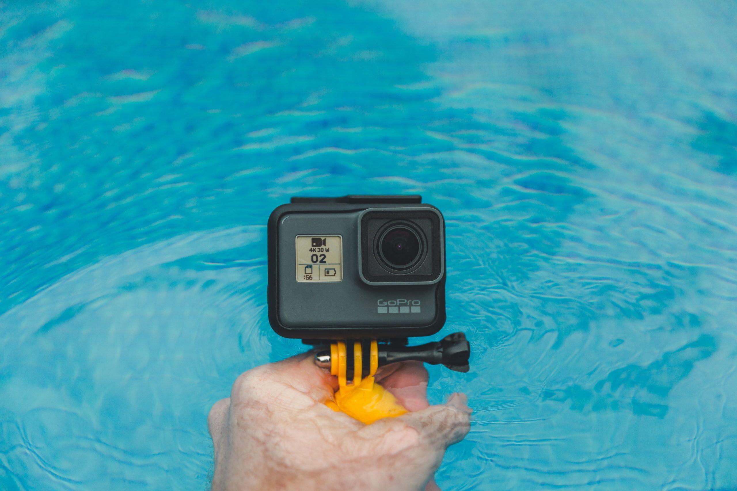 Imagem mostra uma câmera Go Pro com um bastão flutuante sendo segurado pelas mãos de alguém.