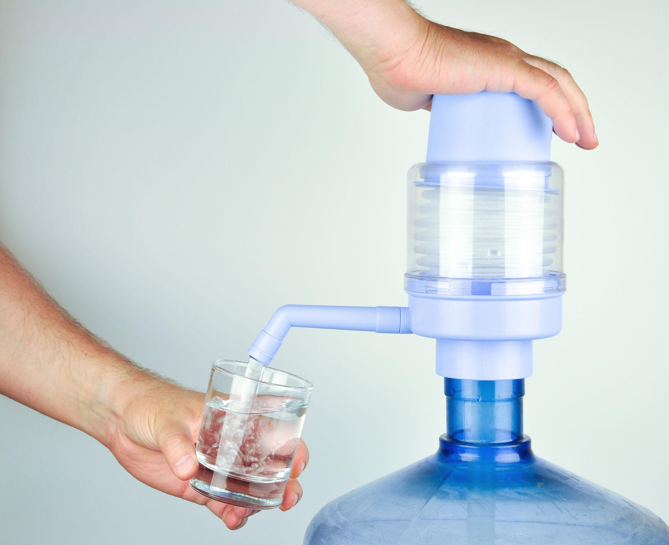 Imagem mostra uma pessoa usando uma bomba de água para galão manual.