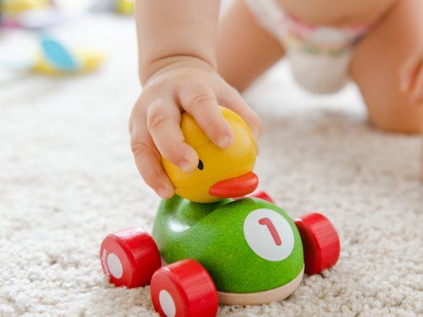 Na foto um bebê brincando com um carrinho de brinquedo.