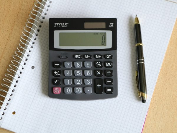 Calculadora de mesa, caderno e caneta.