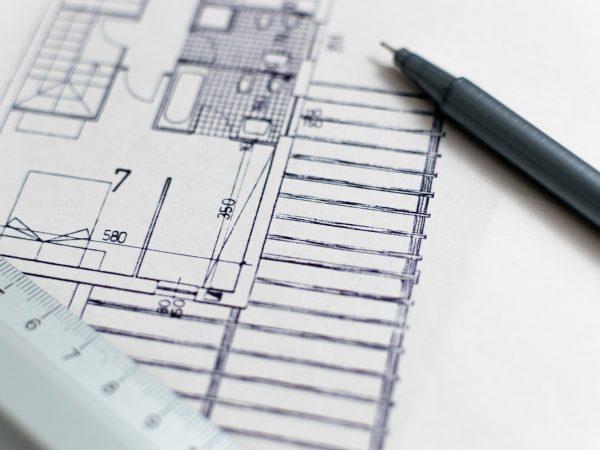 Imagem mostra uma régua, um desenho de arquitetura e uma caneta ponta fina aproximados