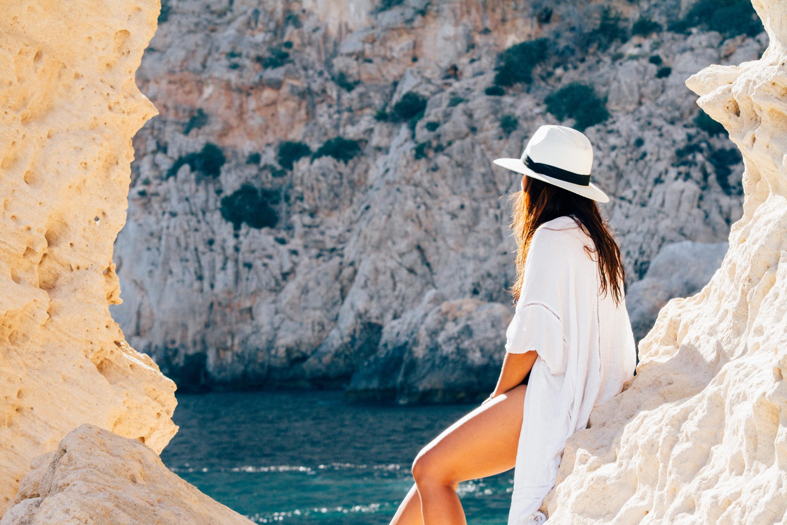 Na foto uma mulher usando uma roupa de praia com um chapéu panamá olhando para o mar.