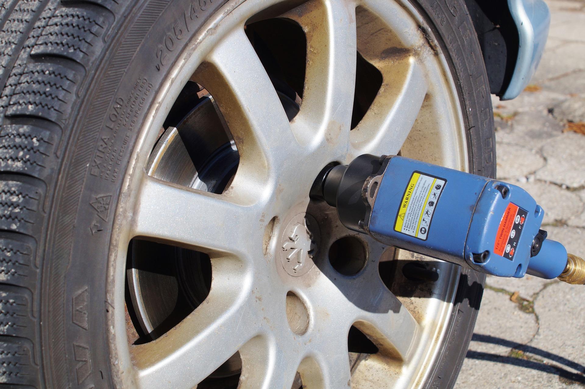 imagem de uma chave de impacto colocada no parafuso de um pneu, para liberá-lo. Neste caso, a ferramenta está parada, sem o utilizador para ativá-la.