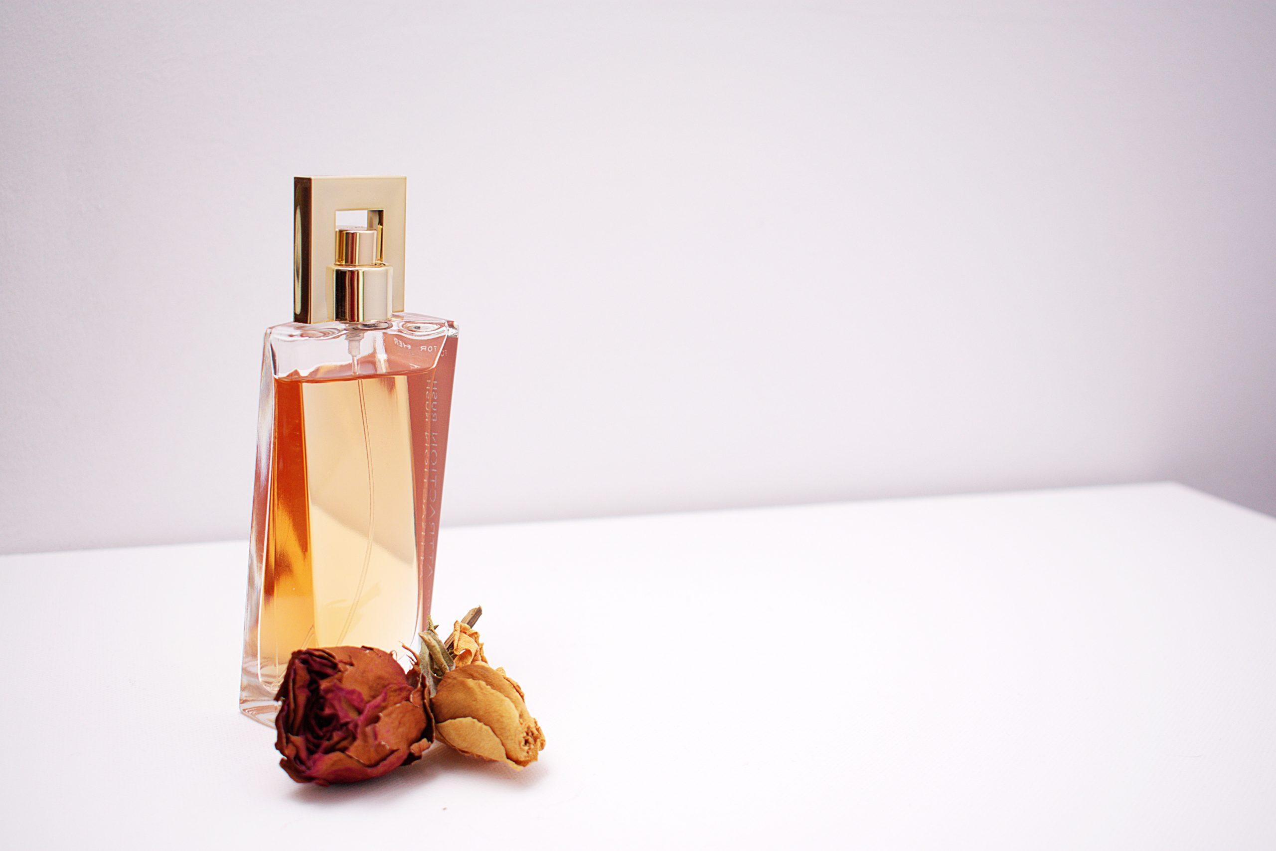 Foto de um vidro de colônia ou perfume, com duas pequenas rosas ao lado, em um local com fundo e superfície brancas.