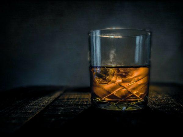 Imagem mostra um copo de whisky preenchido pela metade.