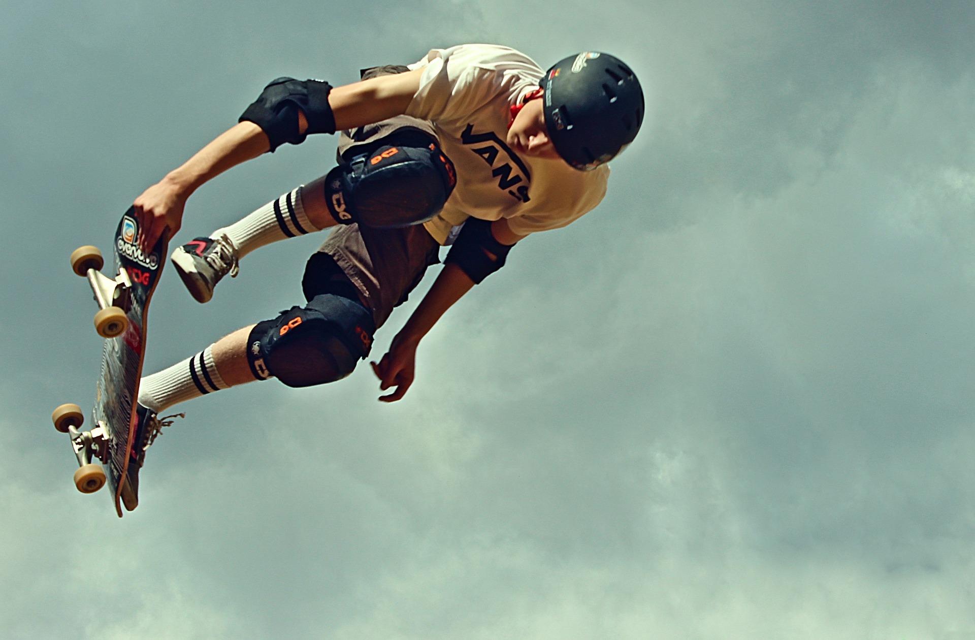 Skatista pratica manobra aérea usando kit de segurança com capacete, cotoveleiras e joelheiras