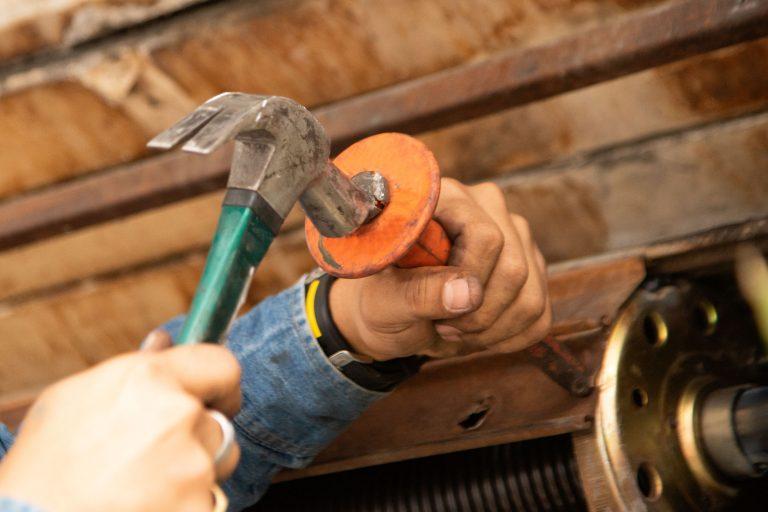 Imagem mostra uma pessoa trabalhando em uma cremalheira de portão.