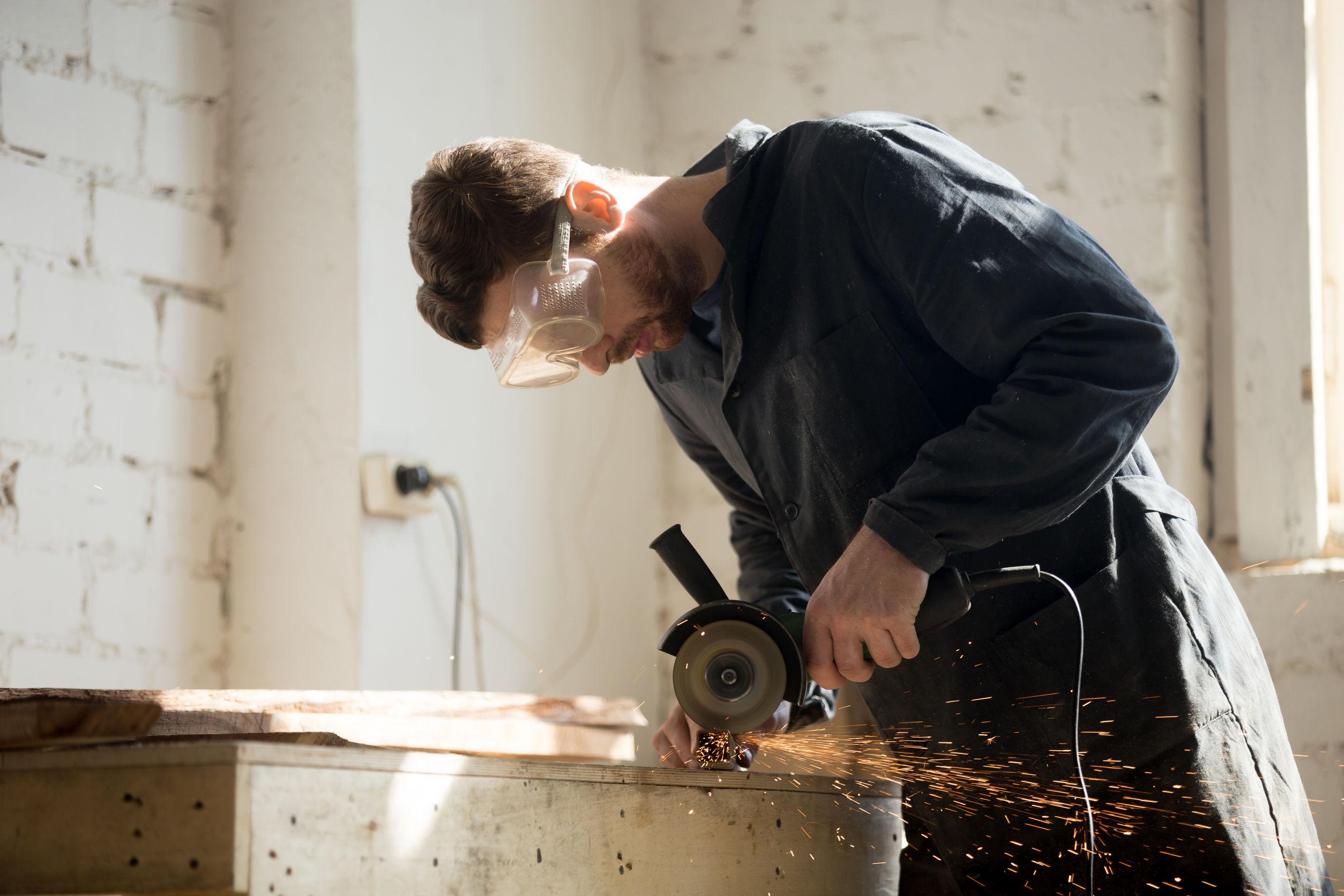 Imagem mostra um homem usando disco de corte para cortar metais.