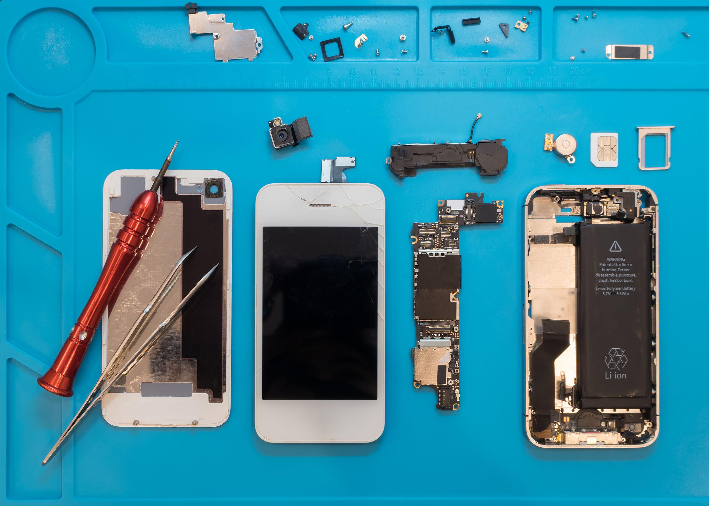Imagem mostra um celular aberto com algumas ferramentas e peças espalhadas sob uma superfície azul