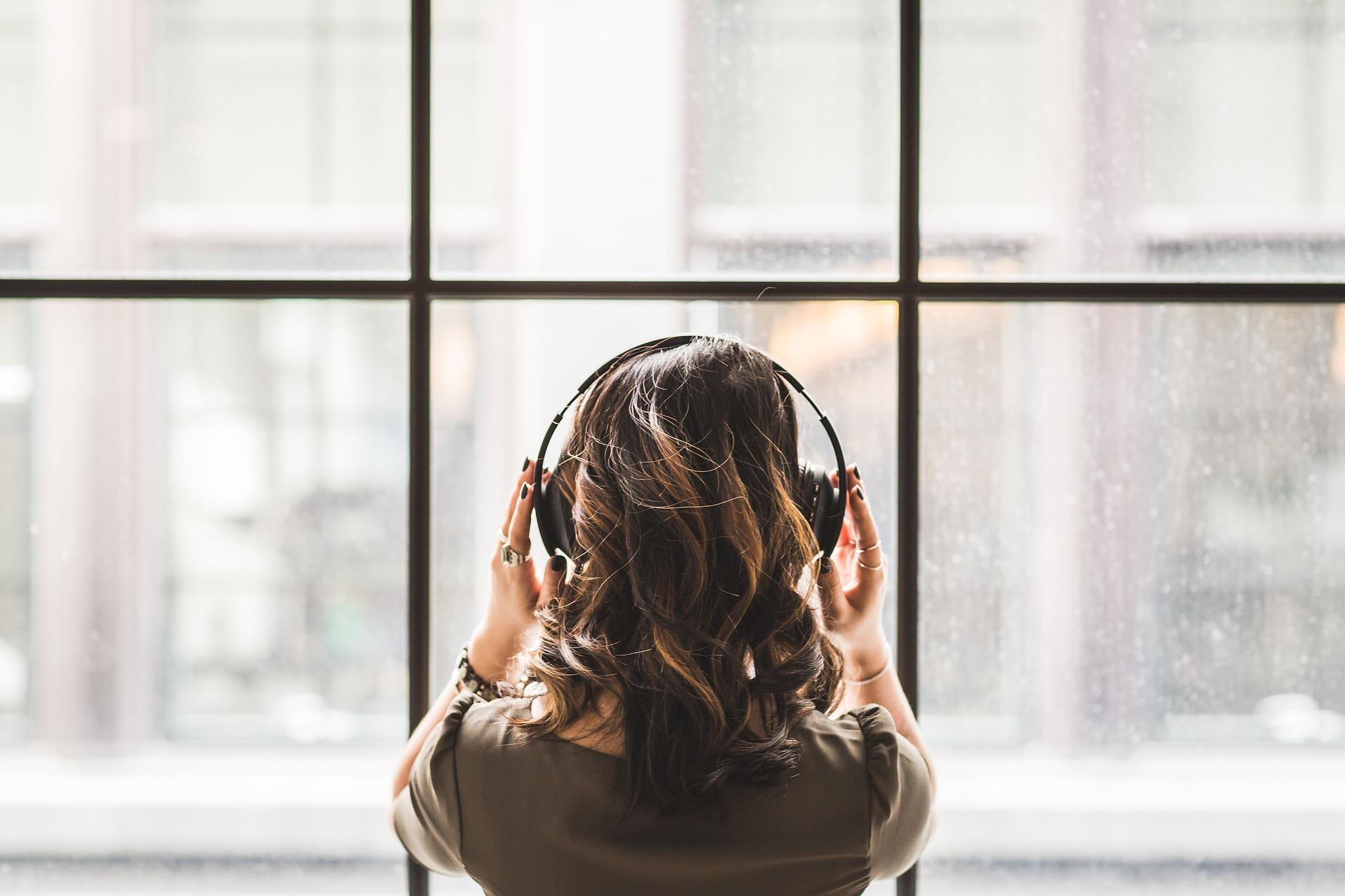 De costas, moça usa fone de ouvido modelo headphone