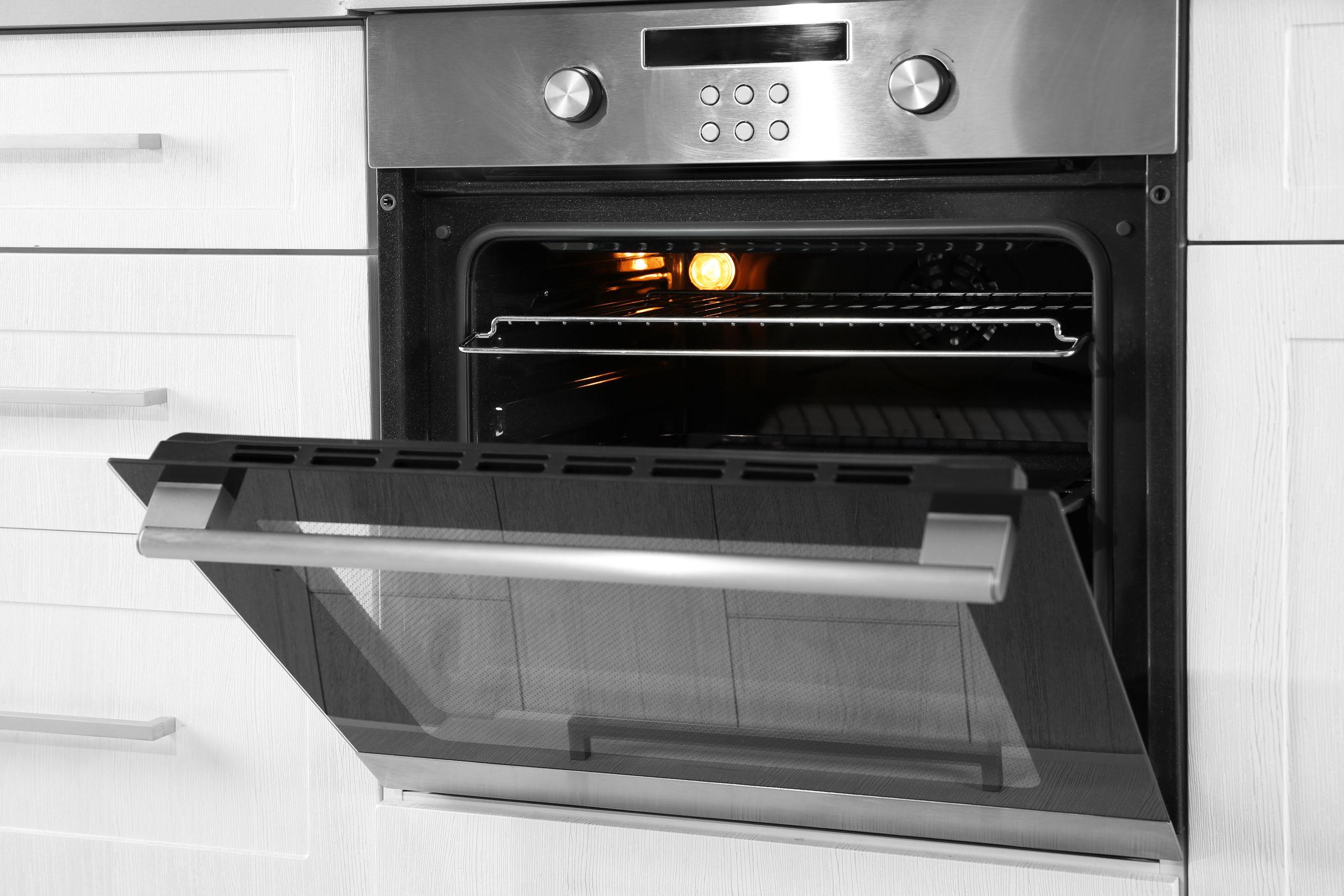 Na foto um forno de embutir em uma cozinha com a porta aberta.