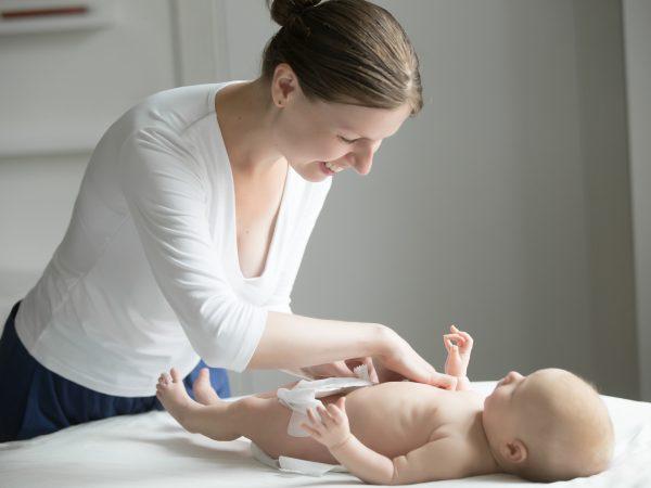 Imagem de mulher sorrindo e trocando a fralda de um bebê que está deitado em uma superfície branca