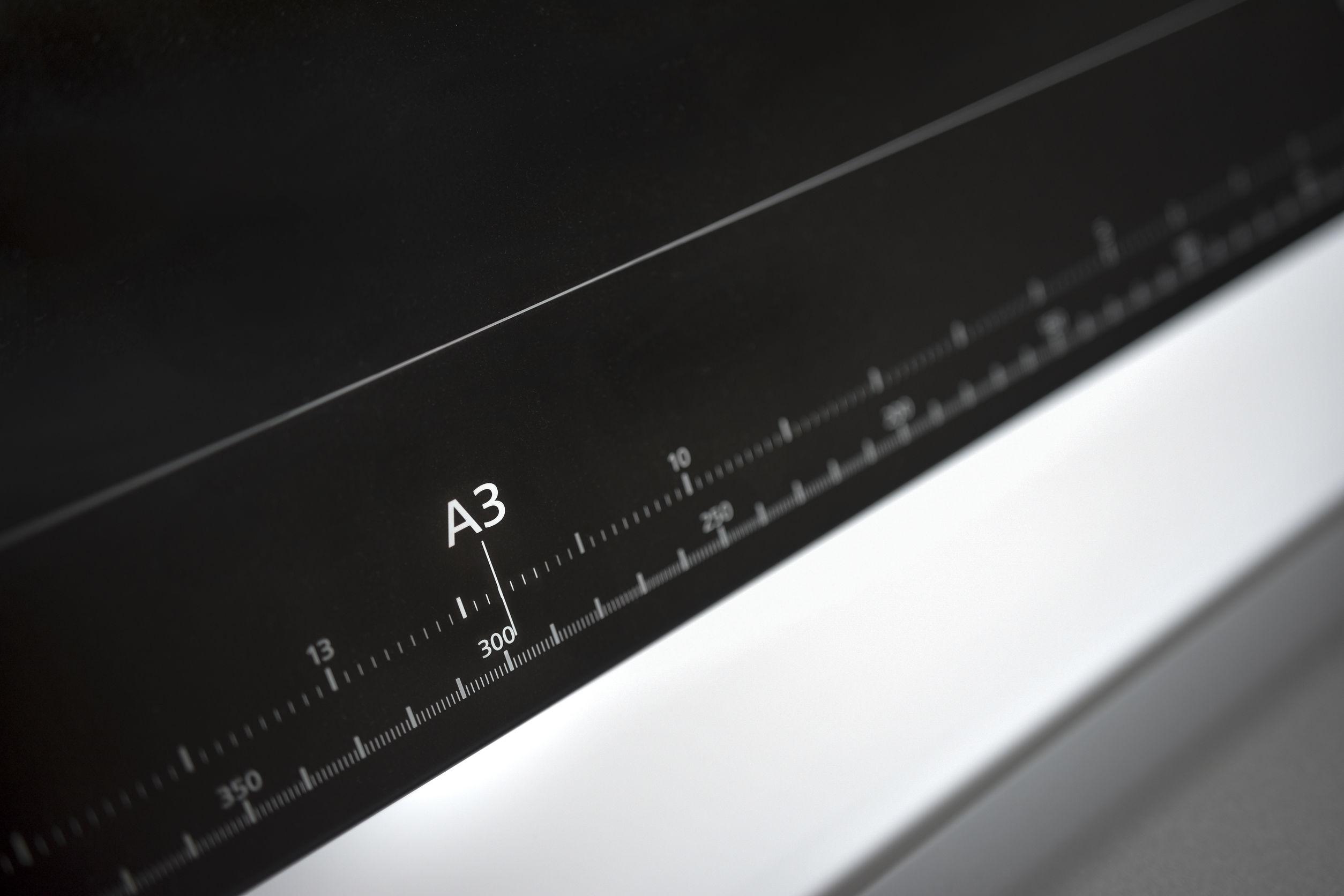 Imagem mostra uma impressora A3 em foco.