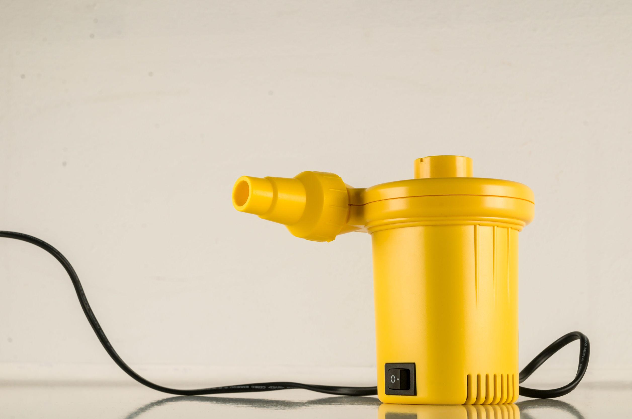 Imagem mostra um inflador amarelo sob uma superfície lisa e um fundo branco.