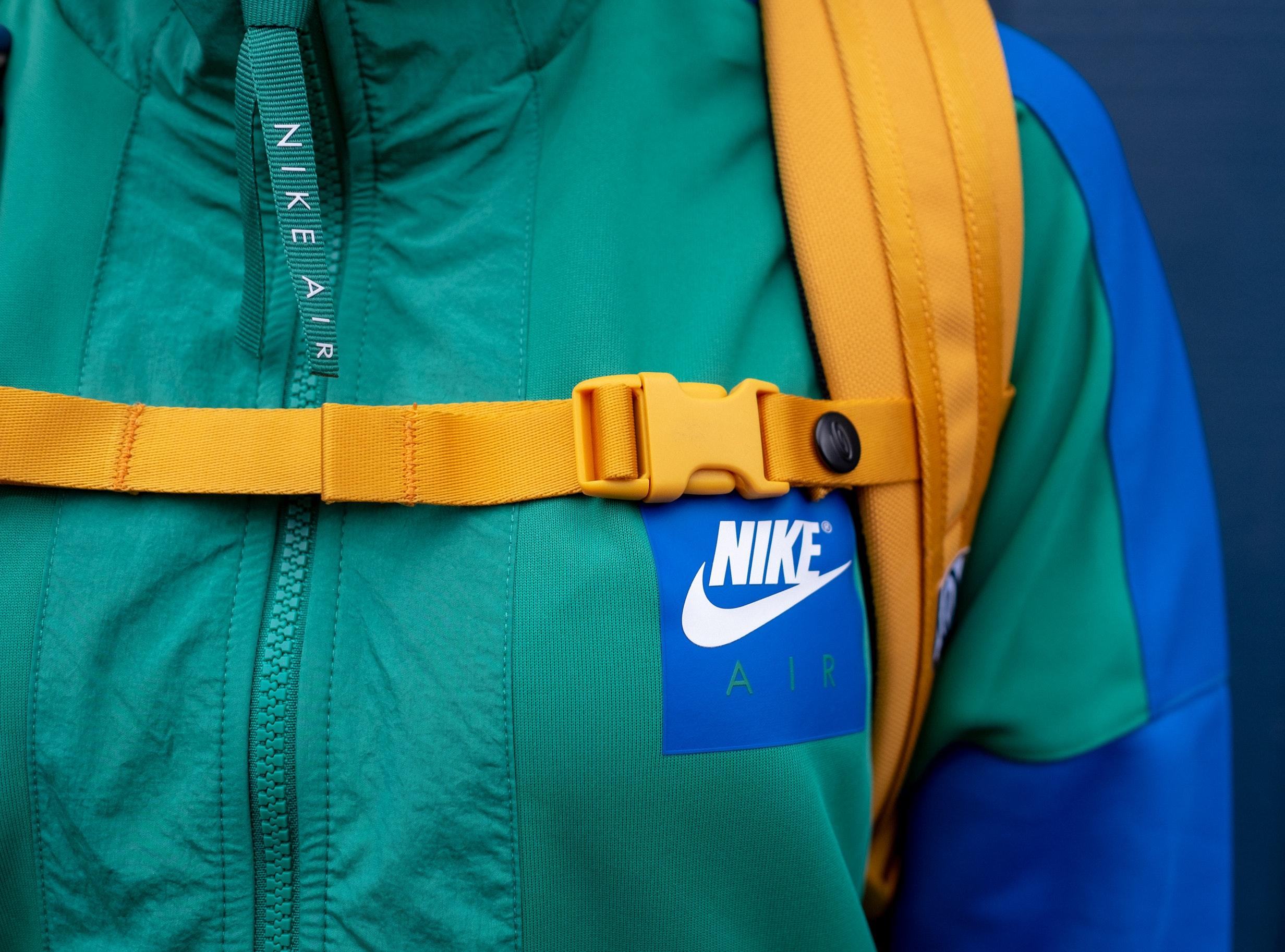 Imagem mostra um close da região peitoral de uma jaqueta Nike, com o logo e o zíper em evidência.
