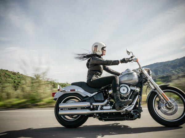 Imagem mostra uma mulher pilotando uma moto e usando uma jaqueta motoqueiro.