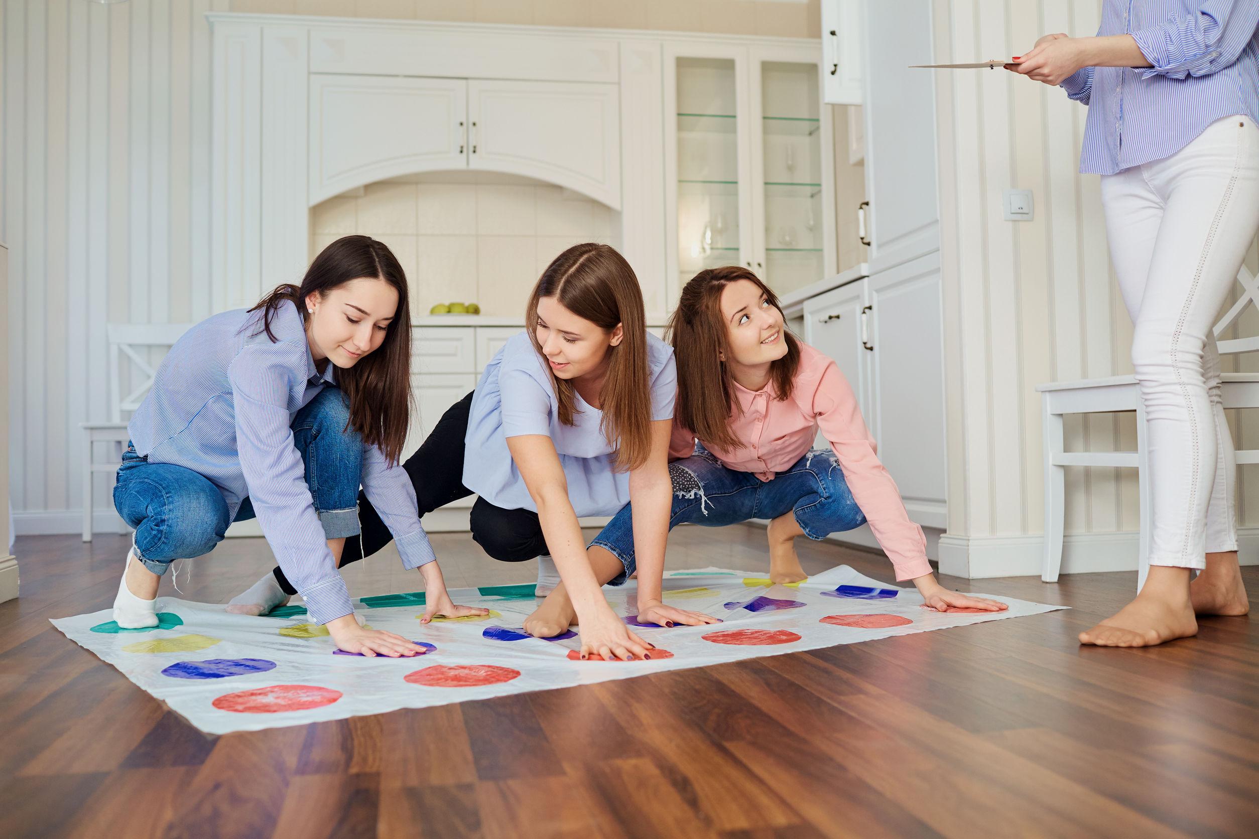 Imagem mostra quatro amigas jogando twister, três no tapete e uma de pé, no comando.