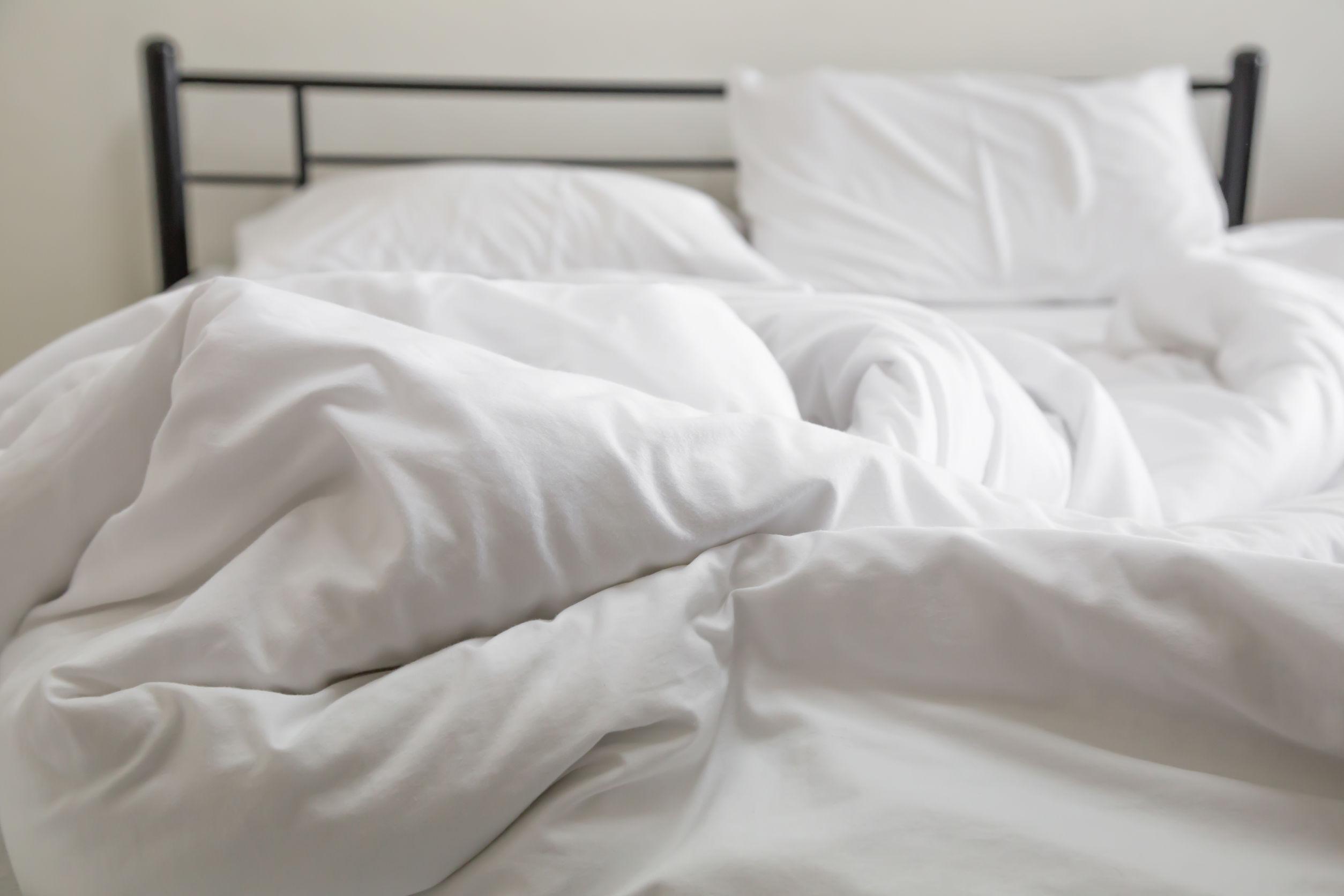 Foto de uma cama um pouco bagunçada, com lençol, travesseiro e edredom brancos.