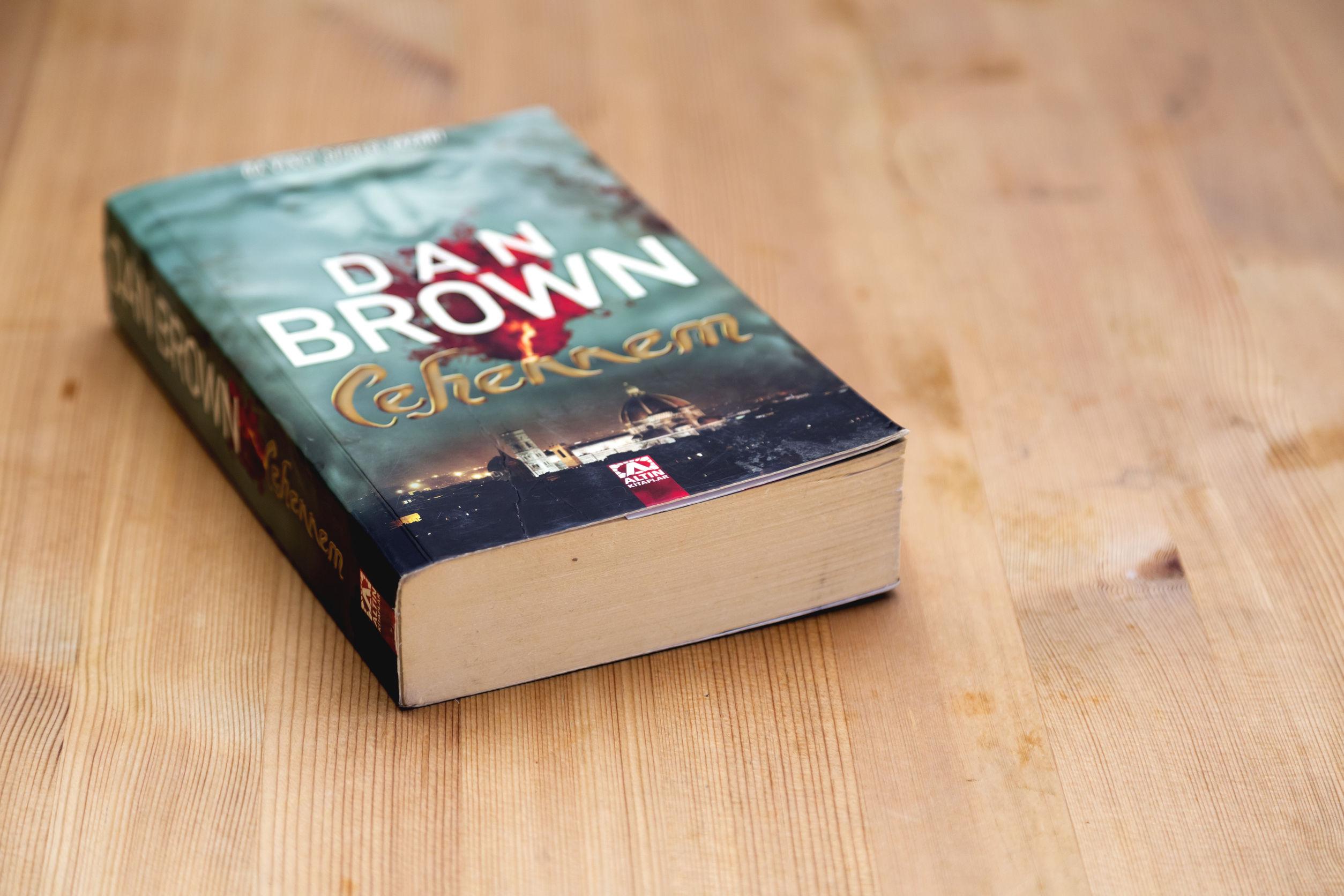 Imagem mostra um livro do autor Dan Brown, com a capa para cima, apoiado numa superfície de madeira.