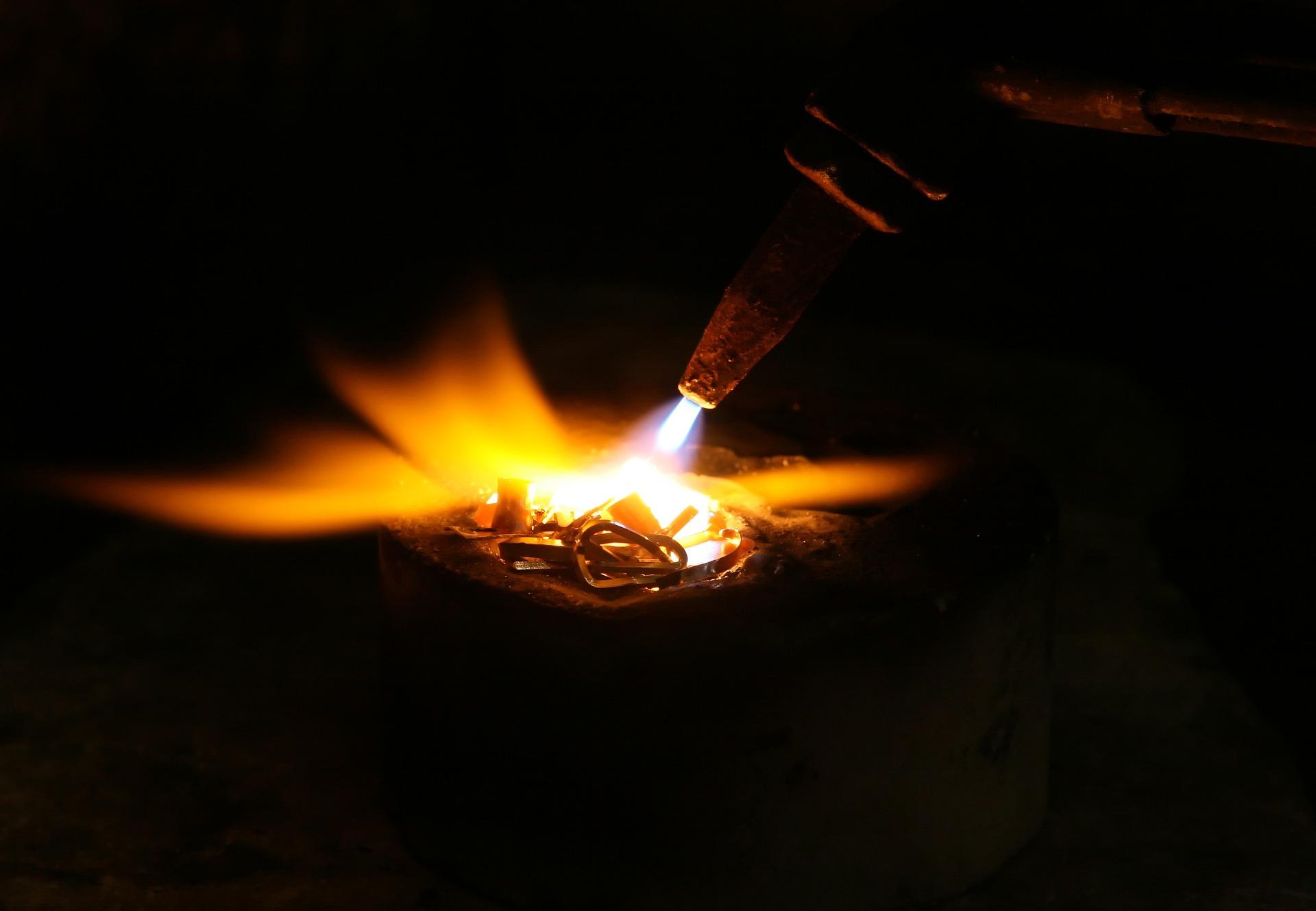 Imagem mostra a chama saindo do bico de um maçarico para uma solda.