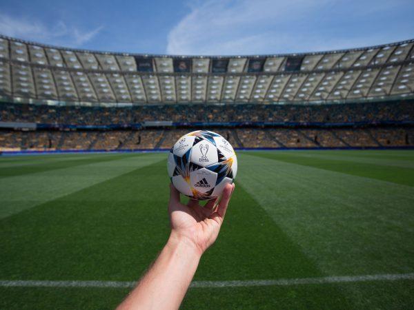 Imagem mostra uma mão segurando uma mini bola, réplica da bola da final da Champions League, em frente ao gramado do campo de um estádio.