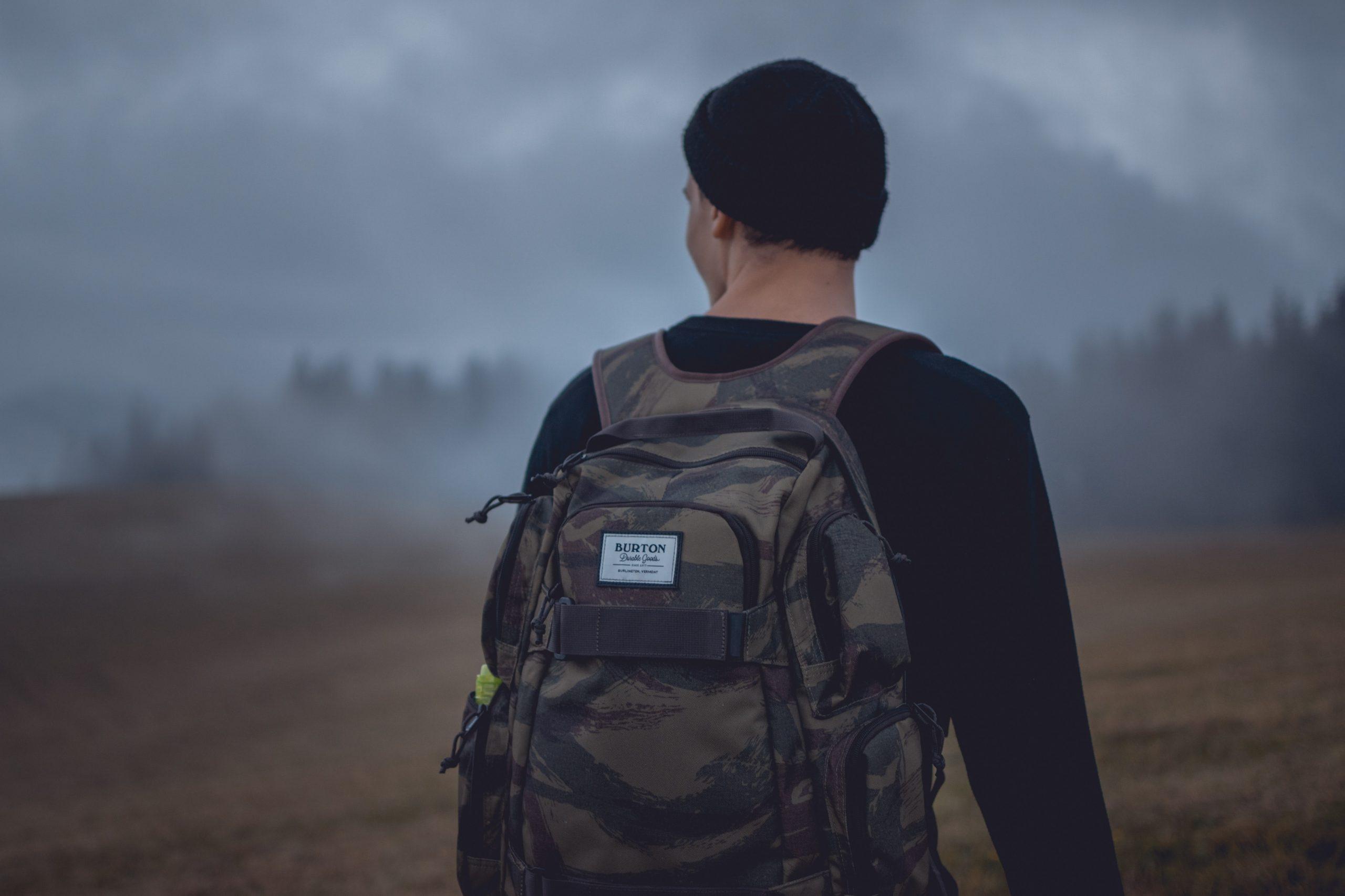 Foto mostra um homem de costas com uma mochila militar em uma paisagem de campo