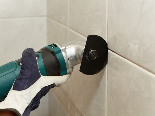 Imagem mostra uma multiferramentas sendo usada para remover azulejos.
