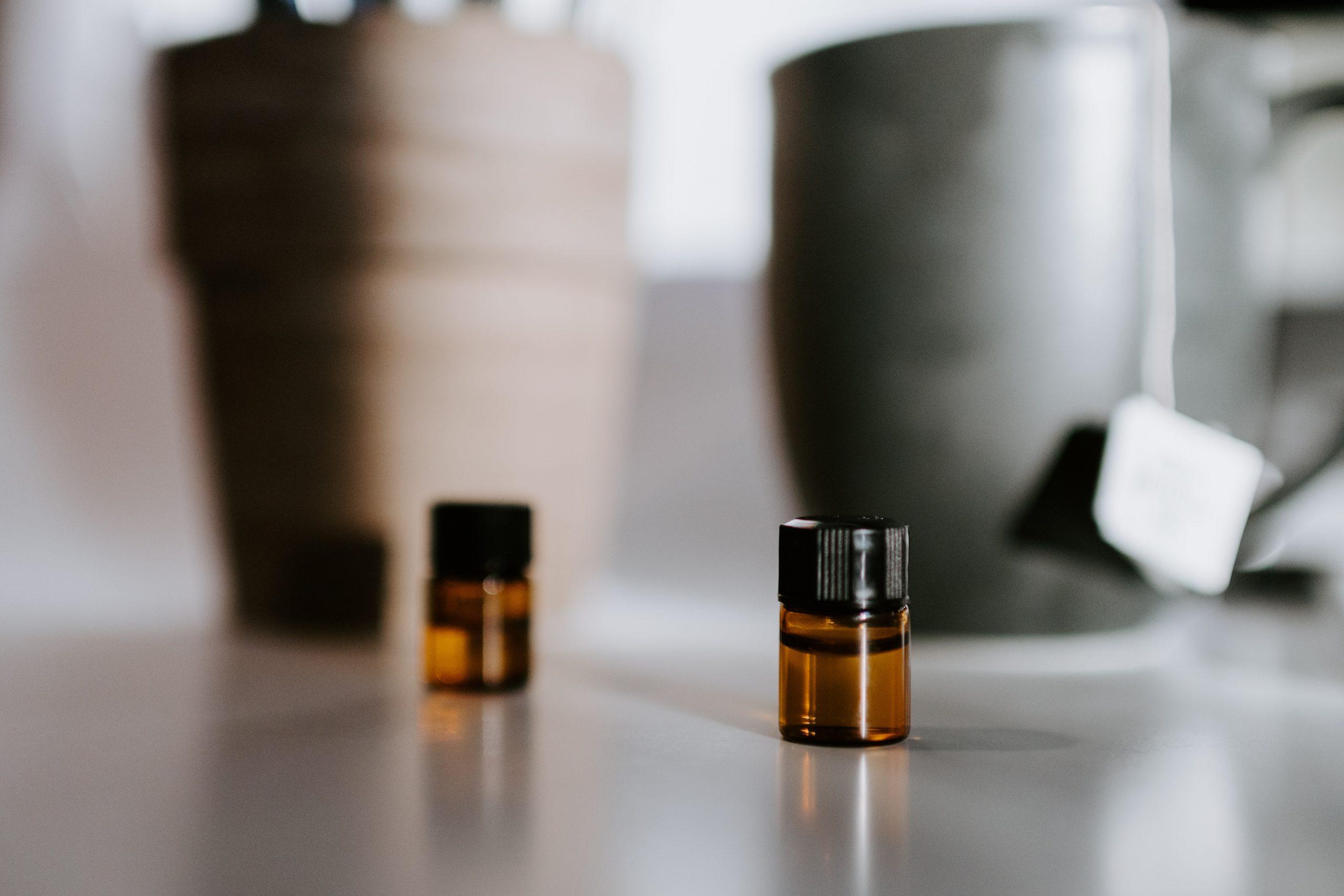 Imagem mostra dois frascos de óleo sob uma superfície lisa, um focado (direita) e outro desfocado (esquerda).