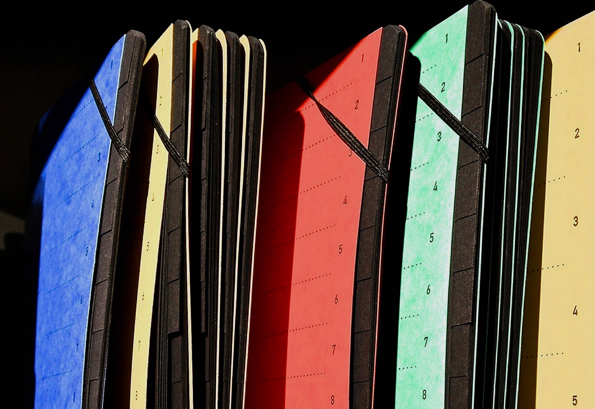 Imagem de pastas sanfonadas coloridas em estante de arquivo