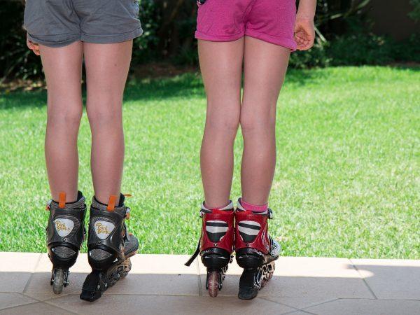 Duas meninas de costas com patins.