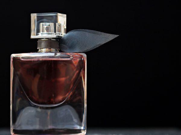 Frasco de perfume com líquido avermelhado em frente a um fundo preto
