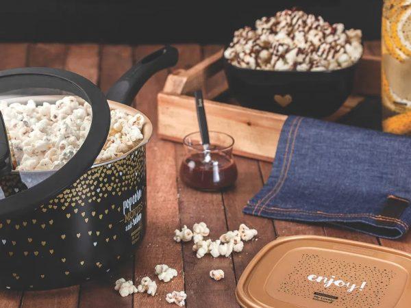 Na foto uma pipoqueira cheia ao lado de uma bandeja com pipocas em cima de uma mesa de madeira.