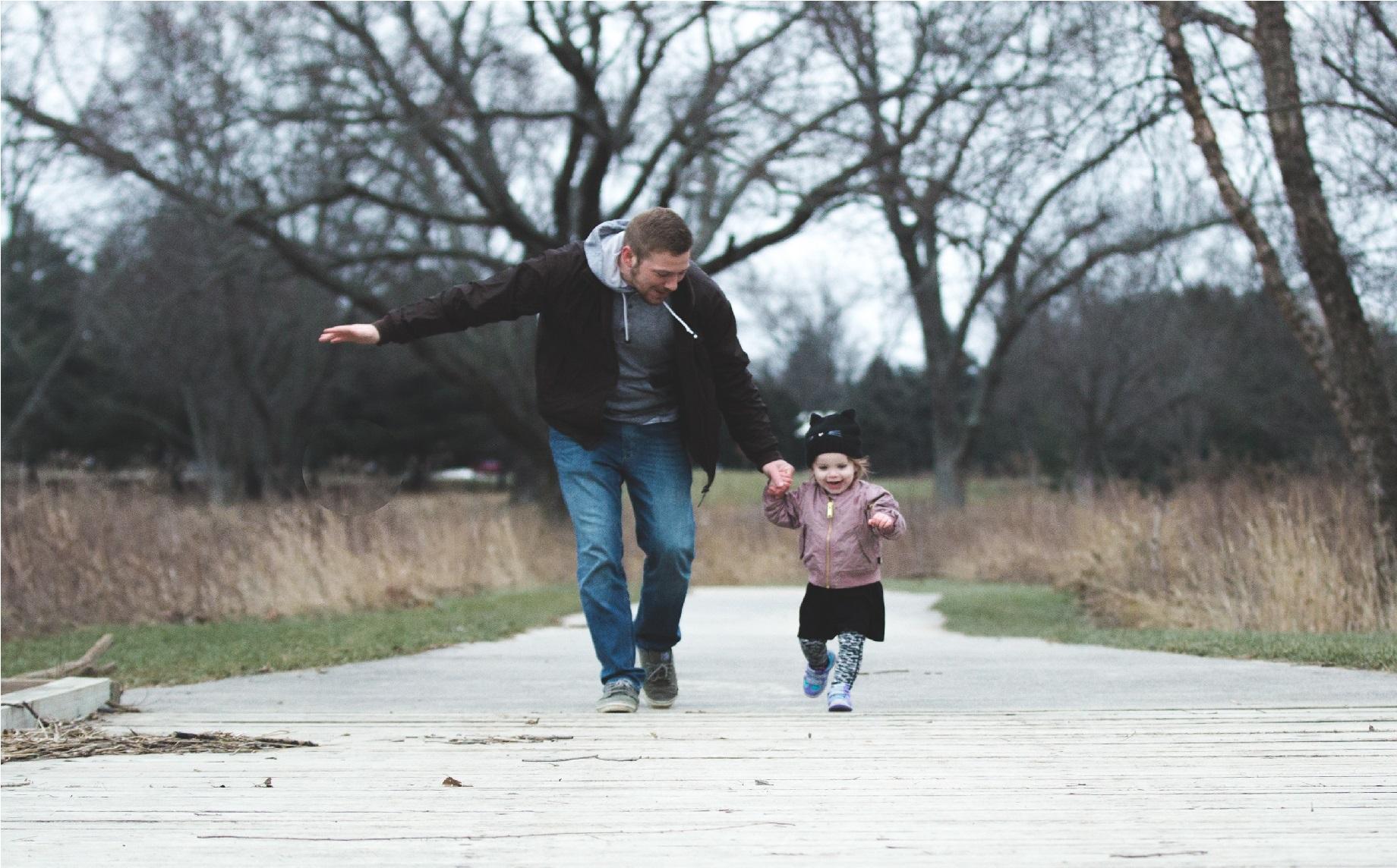 Na foto um pai com uma filha pequena correndo.