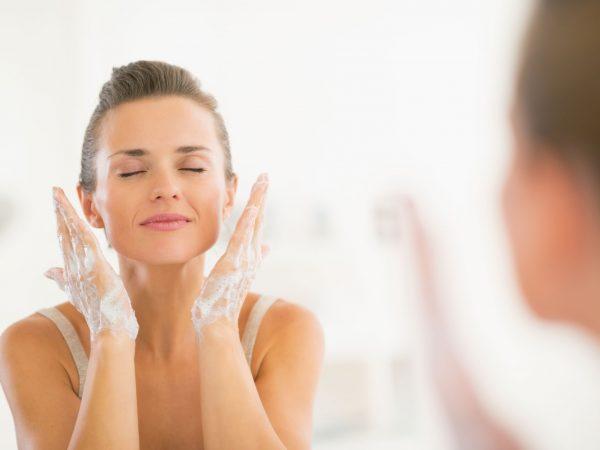 Foto de uma mulher de cabelo preso, olhos fechados e mãos ensaboadas, prestes a lavar o rosto.