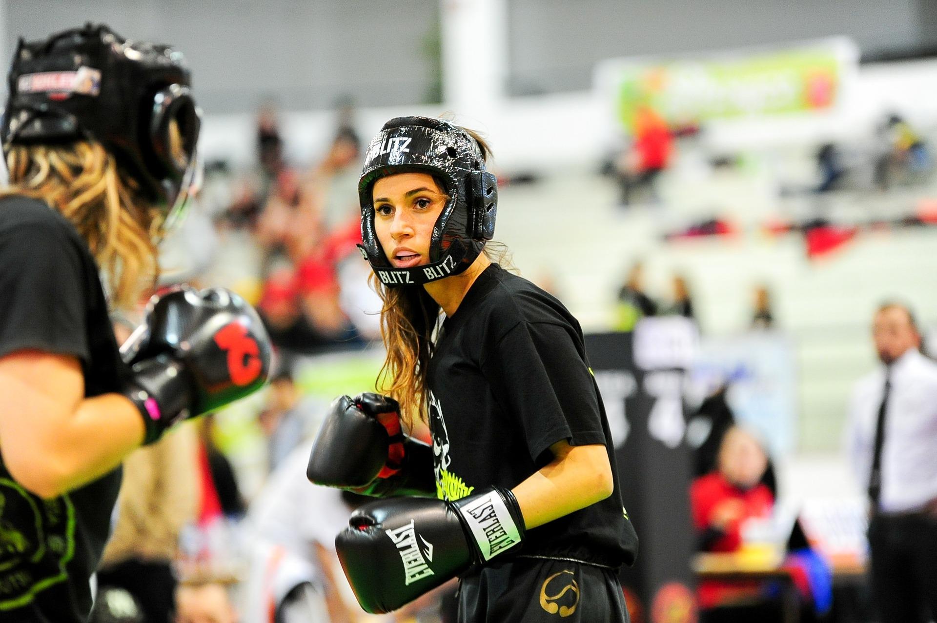 Imagem mostra duas mulheres praticando um esporte de combate.