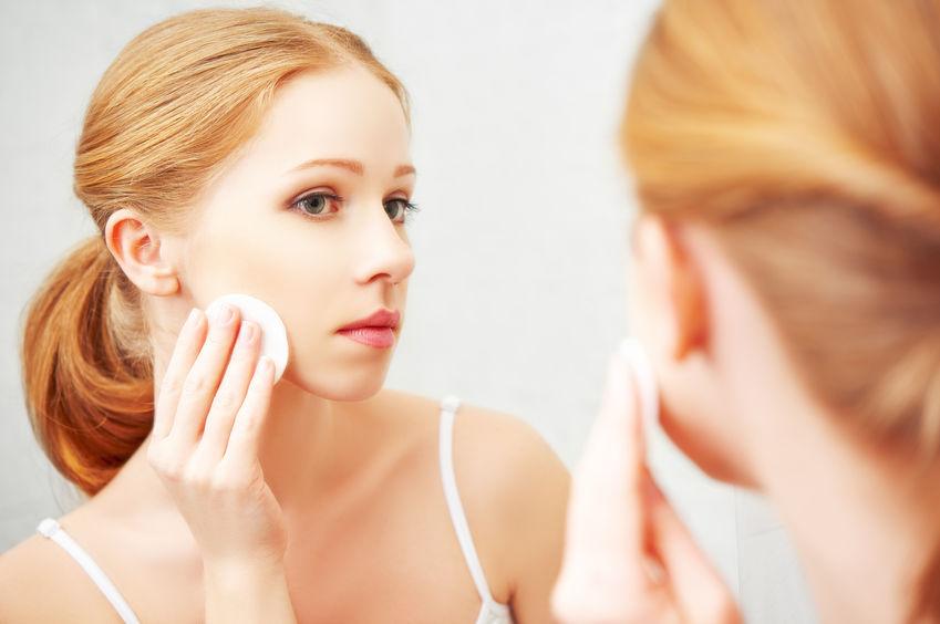 Foto de uma mulher ruiva, de cabelos presos, se olhando no espelho e aplicando um produto na pele com o auxílio de um algodão.