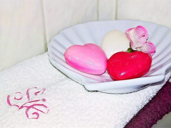 Saboneteira de louça branca em formato de concha disposta sobre toalhas e acomodando três sabonetes em formato de coração
