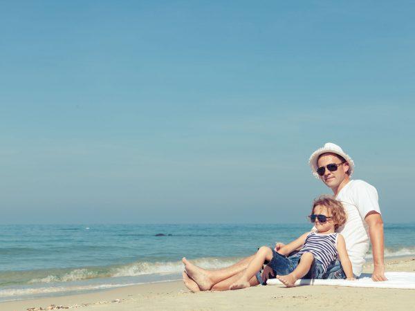 Pais e filho na praia curtem sombra de guarda sol fixado com saca areia