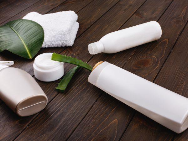 Imagem com vários frascos brancos de diferentes formatos sob uma superfície de madeira marrom escura, ao lado de um potinho com creme e de algumas folhas