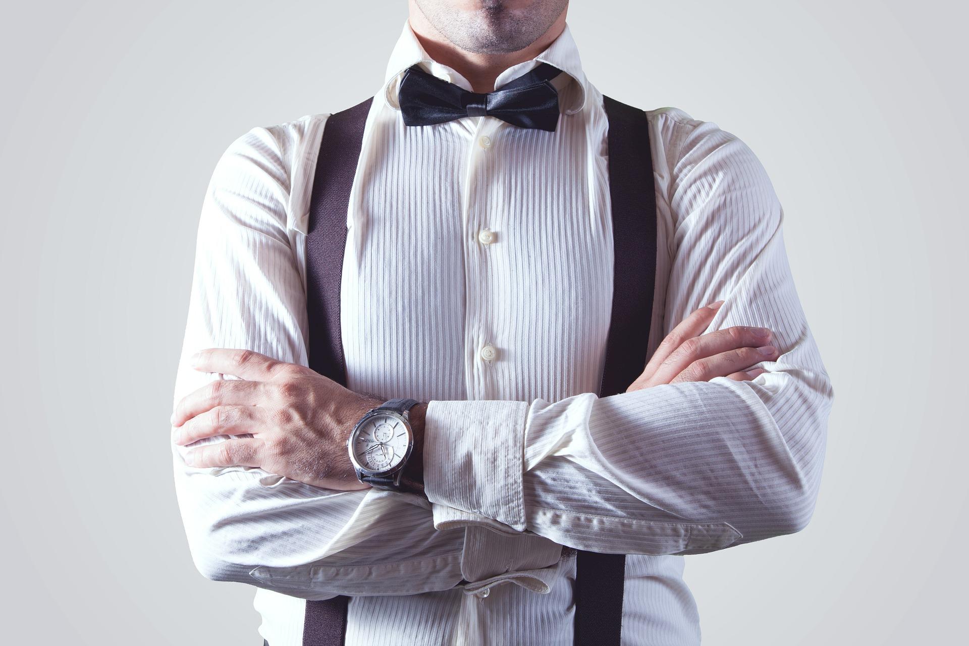 Imagem mostra um homem usando um suspensório com gravata borboleta e camisa de alfaiataria.