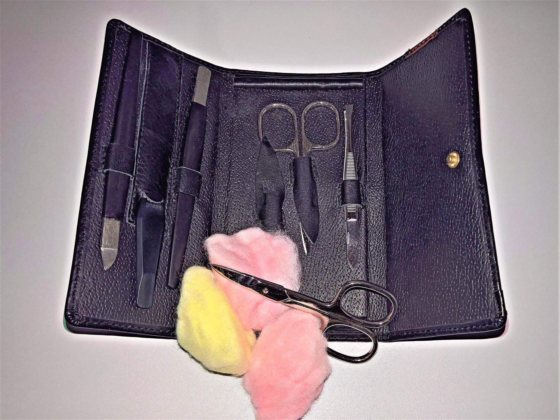 Kit de unha em estojo de couro com tesourinha apoiada em algodão à frente
