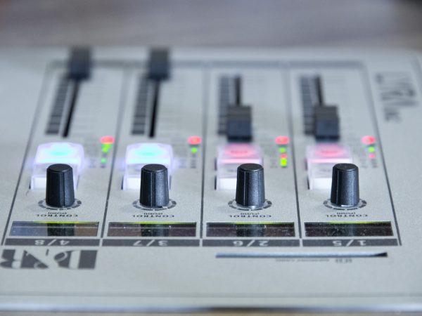Imagem mostra, em foco seletivo, os controladores dos canais de uma pequena mesa de som.