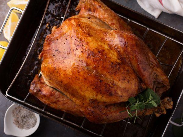 Na foto um frango assado dentro de uma assadeira.