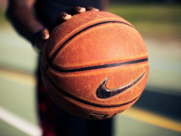 Imagem mostra o close de uma bola de basquete Nike sendo segurada por apenas uma das mãos de uma pessoa, que por sua vez segura a bola bem em frente à câmera.