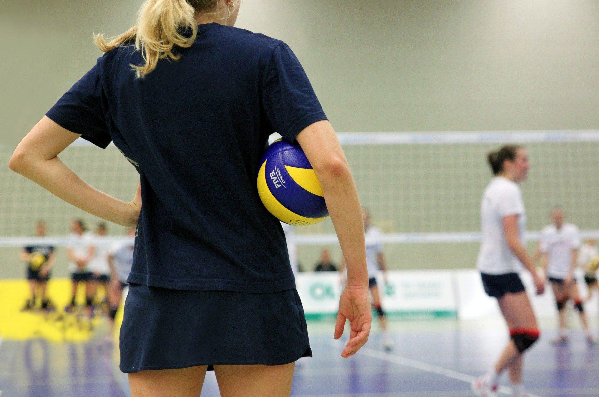 Na foto uma jogadora de vôlei com uma bola embaixo do braço.