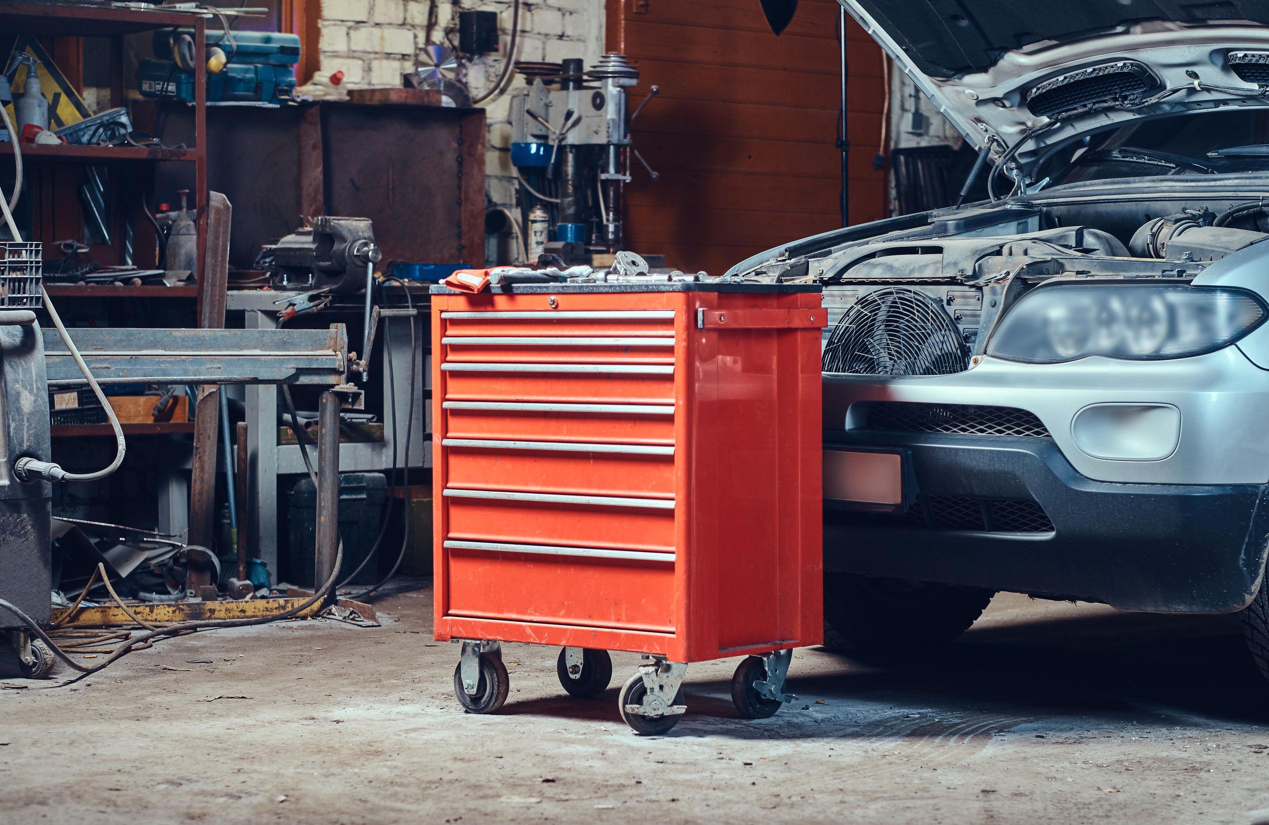 Imagem mostra uma caixa de ferramentas com rodas em uma garagem em frente a um carro.