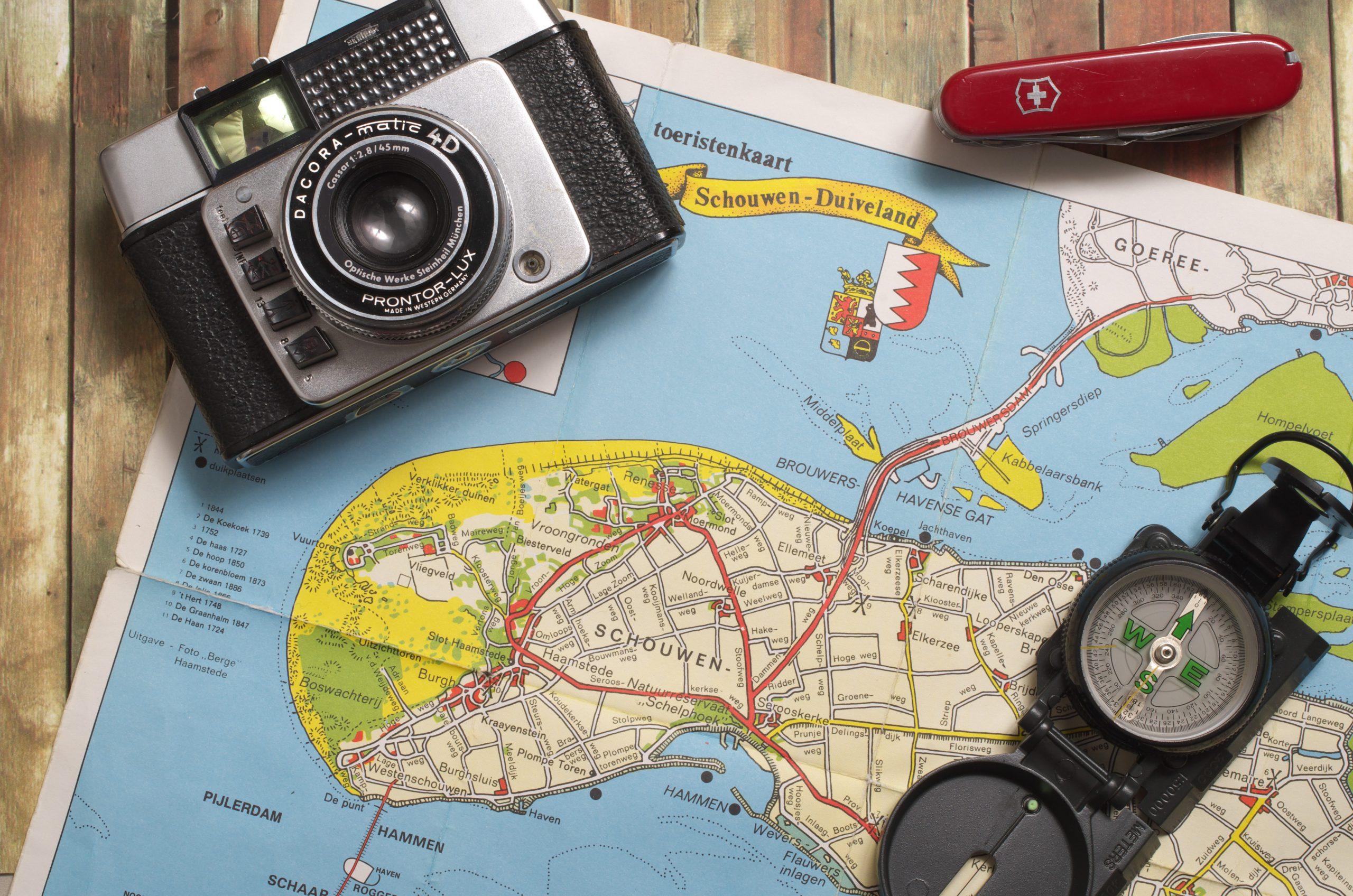 Imagem mostra um canivete Victorinox junto com um mapa, uma câmera e uma bússola.