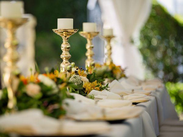 Na foto alguns castiçais dourados em cima de uma mesa.